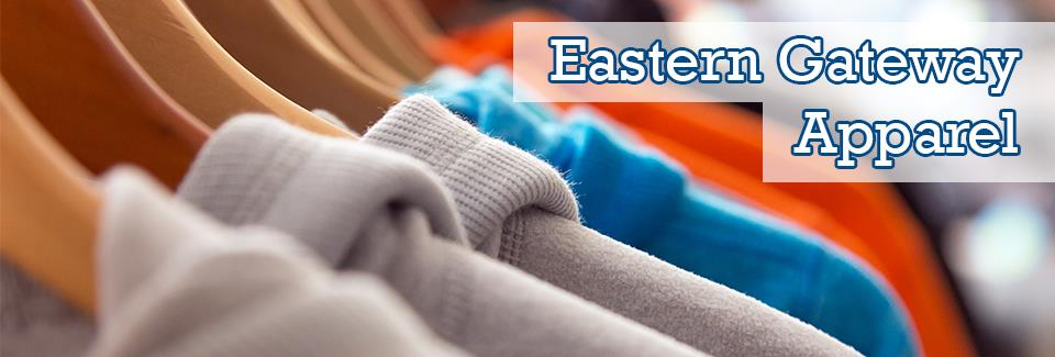 "Wooden shirt hangers with gray, blue and orange hooded sweatshirts on a clothing rack, with the words ""Eastern Gateway Apparel"" on the right side of the slideshow banner."